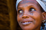 A Fulani woman in Torodi, Niger looks out the door of her house.  She sports the traditional facial scarring, that is considered beautiful. The scarring is done with a razor blade, and charcoal powder mixed with cream is rubbed into the fresh wound to create the darkened effect.  She also has had her lower lip died black. This is done by piercing the lip with a needle in multiple locations, and then rubbing into the dried wounds the ground seeds of a certain tree to blacken it.  Torodi is a town 60 km southwest of Niger's capital, Niamey, on the main road from Niamey to Ouagadougou (the capital of Burkina Faso). Torodi hosts a weekly Friday market, attended in force by people in the surrounding villages.