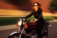 A motorcyle rider speeds down a blurred roadway.