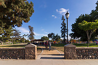 To kids, one on a bike and the other on a skateboard, head in along a decomposed granite pathway entering South Gate Park. The park is full of people: families having picnics under the picnic structures and kids playing on the playground.