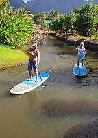Man and woman stand up paddleboarding on the Hanalei River, Kaua'i