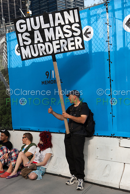 """A protester holds a sign alleging """"Giuliani is a mass murderer""""."""