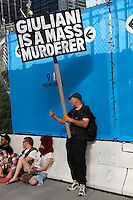 "A protester holds a sign alleging ""Giuliani is a mass murderer""."