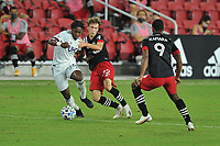 WASHINGTON, DC - SEPTEMBER 27: De Juan Jones #24 of New England Revolution battles for the ball with Griffin Yow #22 of D.C. United during a game between New England Revolution and D.C. United at Audi Field on September 27, 2020 in Washington, DC.