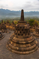 Borobudur, Java, Indonesia.  Stupas on Upper Terrace of the Temple Awaiting Sunrise.  The diamond-shaped holes symbolize the passions that still linger as men rise toward Nirvana.  On the next higher terrace the holes in the stupas are square, symbolizing  the overcoming of passions as one approaches Nirvana.