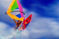 Spectacular shot of windsurfer Steve Villager shooting his colorful sailboard out of an explosion of water at 'Backyards', Sunset Beach, on the north shore of Oahu.