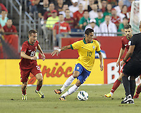 Brazil forward Neymar (10) dribbles as Portugal defender Joao Pereira (21) closes. In an international friendly, Brazil (yellow/blue) defeated Portugal (red), 3-1, at Gillette Stadium on September 10, 2013.