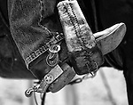 A cowboy rests his spur clad boot in the stirrup.