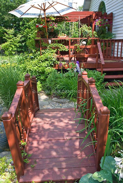 Darling garden bridge walkway path in small backyard garden with deck, house, umbrella, on sunny summer day