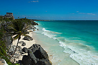 Iconic, pre-Columbian Tulum Mayan temple of the god of the winds, above the turquoise Caribbean Sea and idyllic, deserted white sand beach, in Mexico