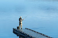 Man flyfishing from a floating dock, Sebago Lake, Standish, Maine, USA.