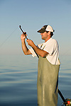 A fisherman fixes a rod while blue fin tuna fishing on the Gulf of St. Lawrence near North Rustico, Prince Edward Island, Canada.