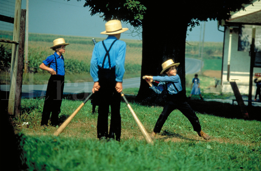 Amish boys aged 10 to 15 play softball at school during recess. Amish children. Lancaster Pennsylvania United States schoolground.