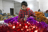 November 28, 2015, Yiwu, China - Zhao Yimin, 15, makes bundles of tinsel by hand at the Xin Shua tinsel factory. She and her mother are migrant workers from Guilin. Zhao attends a middle school for migrant worker, but has worked at the tinsel factory since she was 11 years old. She is paid 0.04 RMB for each bunch of tinsel she tags tog ther by hand and her tally is added to that of her mother.     Photo by Dave Tacon / Sinopix