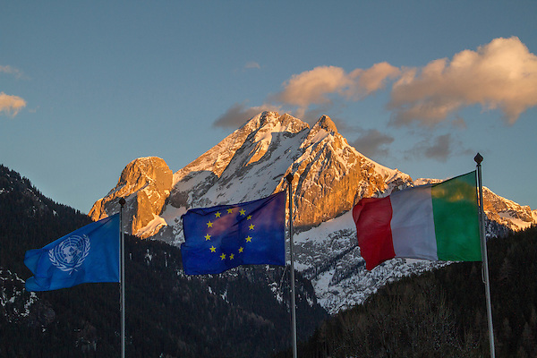 Italy, Dolomites.  <br /> Make a more unique composition by adding a foreground to a beautiful sunset.  Italian and EU flags with Mount Marmolada, Canazei, Italy.