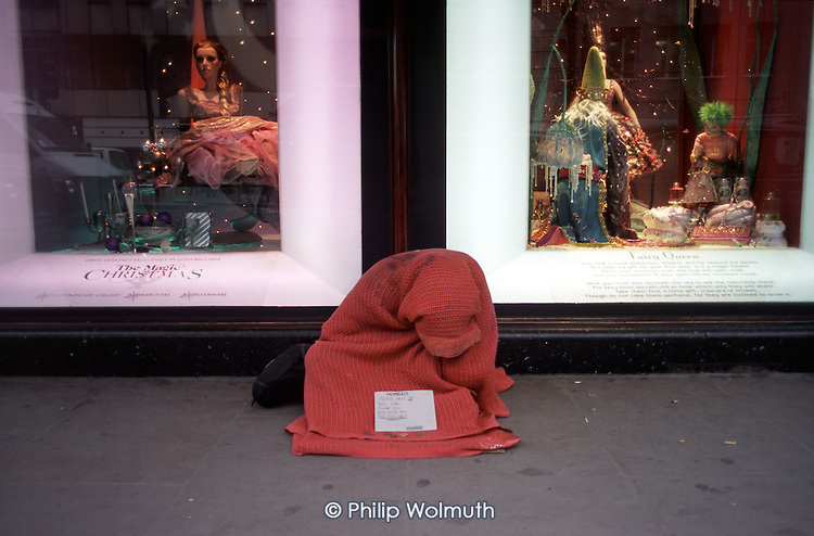 Homeless person begging outside the Harrods department store in Knightsbridge, London, during the Christmas shopping season.