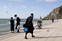 An Hasidic family walk along the promenade by the beach in Aberystwyth.