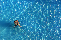 A couple holds eachother tight as they stand alone in a hotel pool in Virginia Beach, Va.