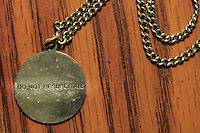 Close-up of medic alert necklace medallion with DNR instructions - Do Not Resuscitate.  Image has been altered to obliterate personal information.