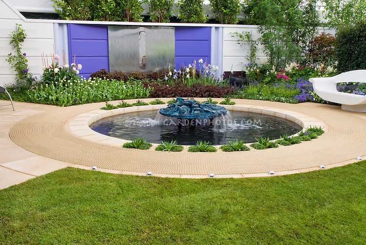 Water fountain garden feature in backyard design, upscale landscaping with modern garden bench, patio decking, flowers and plants. Fleming's Nurseries Australian Garden.Outdoor lifestyle garden, Chelsea Flower Show 2006. Design: Dean Herald.Outdoor Lifestyle