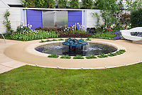 Water fountain garden feature in backyard design, upscale landscaping with modern garden bench, patio decking, flowers and plants. Fleming's Nurseries Australian Garden.Outdoor lifestyle garden, Chelsea Flower Show 2006. Design: Dean Herald.Outdoor Lifestyle