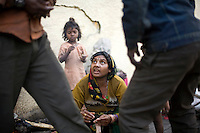 A homeless woman argues with her husband whilst butchering a chicken's entrails to cook by the side of the road at a temporary shelter in Karol Bagh, New Delhi.