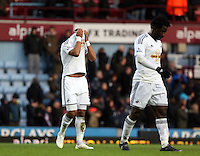 Sunday 07 December 2014<br /> Pictured L-R: DIsappointed Swansea players Ashley Williams who hides his head in his shirt and team mate Wilfried Bony walk off the pitch after the final whistle <br /> Re: Premier League West Ham United v Swansea City FC at Boleyn Ground, London, UK.