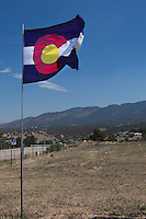 A Colorado state flag flies against a blue sky along a rural highway near Canon City, Colorado.