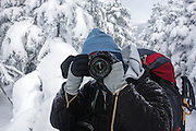 A hiker photographing along the Carter-Moriah Trail in winter conditions near the summit of Carter Dome in the White Mountains, New Hampshire USA