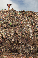 Nigeria. Enugu State. Enugu. Garbage collector on garbage heap. Scavenger at work. A lonely woman on rubbish landfill. The open air and uncontrolled rubbish dump shows the failure in the solid-waste management. Enugu is the capital of Enugu State, located in southeastern Nigeria.  2.07.19 © 2019 Didier Ruef