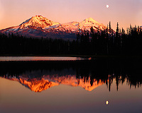 Sunset glow and reflection of moonrise over The Sisters at Scott Lake; Willamette National Forest, OR