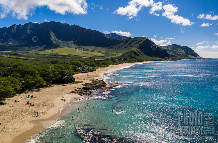 Beachgoers enjoy Makua Beach and Bay, West O'ahu, seen from above on a sunny day.