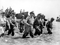 """October 1944 - Exact Date Shot Unknown - Gen. Douglas MacArthur wades ashore during initial landings at Leyte, Philippine Islands, soon after American forces swept ashore from a gigantic liberation armada into the central Philippines, at the historic moment when the General made good his promise """"I shall return"""".  1944. (Coast Guard)"""