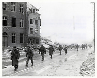 .S. Inf troops of the 30th Infantry Division on march through Malmedy which was leveled in error by U.S. bombers.<br /> 29 December 1944