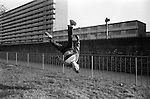 Teen girl playing in street 1980s UK. She is practicing gymnastics and is head over heals doing a somersault turning cart wheels south Heygate Estate, Walworth south London 1983