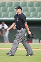Home plate umpire Aaron Larsen walks out to the mound to break up a meeting during a South Atlantic League game between the Hagerstown Suns and the Kannapolis Intimidators at Fieldcrest Cannon Stadium August 8, 2010, in Kannapolis, North Carolina.  Photo by Brian Westerholt / Four Seam Images