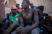 Sub-Saharan illegal migrants sit at a crossroad as they queue for daily job in the streets of Sabha City, Libya.