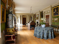 A gallery decorated with classical columns displays a collection of gilt-framed paintings and sculpture