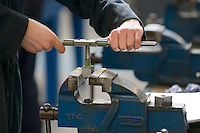 Tapping a hole in a steel block using a tap and tap wrench.  Apprentice engineering students at Kingston College..