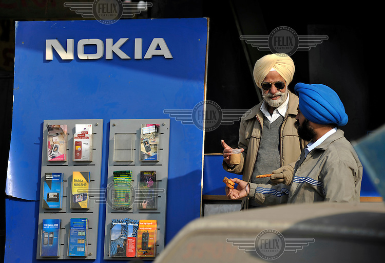 Sikh men with turbans drink tea outside a mobile phone shop.