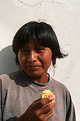 Pimentel, Peru. Smiling Amerindian man eating sweetcorn (maize).