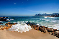 Wave over golden sand and rocks at Ipanema Beach with the Two Brothers Mountain in the background, Rio de Janeiro, Brazil