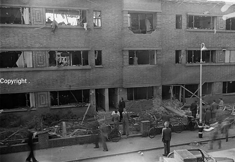 Photo from the NIOD's Huizinga collection. German soldiers and residents are facing a damaged apartment complex after a V2 impact. Menno Huizinga was part of the Hidden Camera and took pictures illegally during the occupation. He did this mainly in his hometown The Hague.