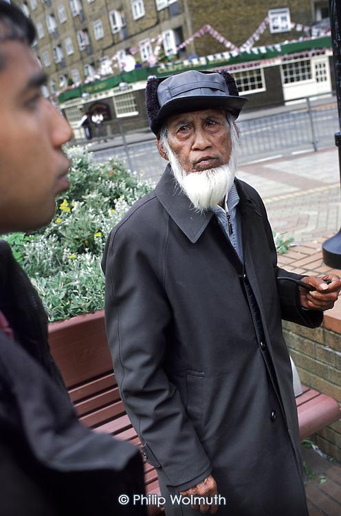 Elderly Bangladeshi man speaks with a Tower Hamlets street warden in Bethnal Green