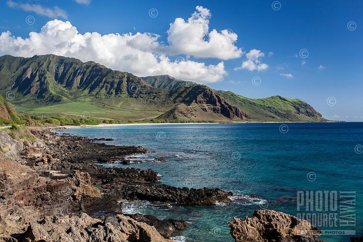 The Wai'anae Mountains embrace the rocky shoreline of Yokohama Bay, West O'ahu.