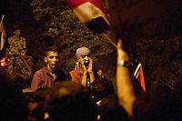 EGITTO, IL CAIRO 9/10 settembre 2011: assalto all'ambasciata israeliana. Migliaia di manifestanti egiziani, ancora infuriati per l'uccisione di cinque guardie di frontiera egiziane da parte dell'esercito israeliano, hanno fatto irruzione nella sede diplomatica israeliana e sono stati poi sgomberati da esercito e polizia egiziana. Nell'immagine: giovani manifestanti la sera della protesta. Dietro di loro alcuni poliziotti egiziani.<br /> Egypt attack to the Israeli embassy  Attaque à l'ambassade israelienne Caire