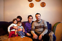 Former refugee Elvis Causevic with his wife Irma and his mother Dzevada (left) holding their daughter Adna (left) and son Aldin in the living room at the family home.<br /> <br /> In 1992 while volunteering at the Varazdin refugee camp Panos photographer Bjoern Steinz met and became close to Elvis, a Bosnian Muslim refugee, and his family. They shared the hardships of camp life together which Steinz documented. While the prints were archived for many years two of the images always returned to Bjoern's thoughts. 25 years later he set out to try and find out what had happened to Elvis and his family in the intervening years. Modern social media made the task surprisingly easy and they were reunited in Hadzici where Elvis now lives with his family.