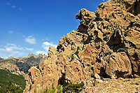 Corsica. Punta Aracale, Bavella.  France. Corse. Strangely weathered volcanic rock formations. Aiguilles de Bavella in the background..