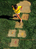 Young African-American girl playing a game of hopscotch.