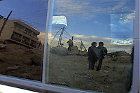 Palestinians are reflected in the window of a car waiting for a security check by Israeli border police, as they cross a road block in Shech Sahed in the outskirts of Jerusalem, March 5, 2003 .Photo by Quique kierszenbaum