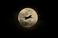A jetliner flies through the full Pink Moon as it made its way to LAX on Thursday April 18, 2019. (Photo by Michael Kitada, Contributing Photographer)